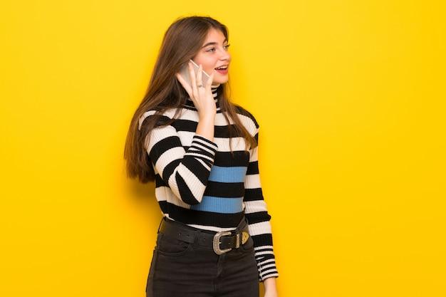 Jovem mulher na parede amarela, mantendo uma conversa com o telefone móvel Foto Premium