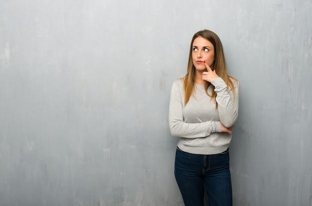 Jovem mulher na parede texturizada com dúvidas enquanto olhando para cima Foto Premium