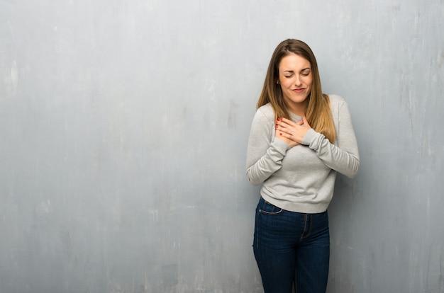 Jovem mulher na parede texturizada com uma dor no coração Foto Premium