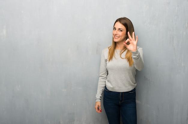 Jovem mulher na parede texturizada mostrando um sinal de ok com os dedos Foto Premium
