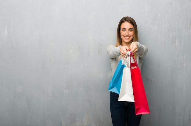 Jovem mulher na parede texturizada segurando um monte de sacos de compras Foto Premium