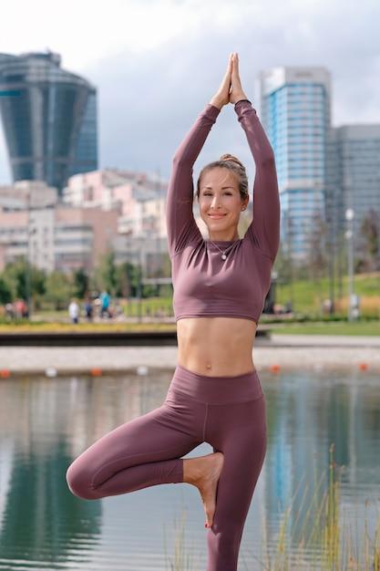 Jovem mulher na pose de ioga de árvore e sorrindo com a cidade. Foto Premium