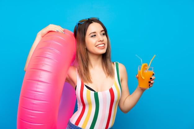 Jovem mulher nas férias de verão na parede azul com cocktail Foto Premium
