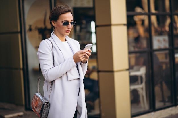 Jovem, mulher negócio, em, agasalho, usando, telefone Foto gratuita