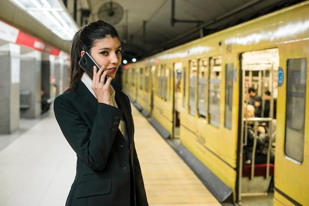 Jovem, mulher negócios fica, em, estação metrô, falando telefone móvel Foto gratuita