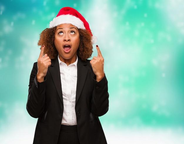 Jovem mulher negra de negócios usando um chapéu de papai noel chirstmas surpreendeu apontando para mostrar algo Foto Premium