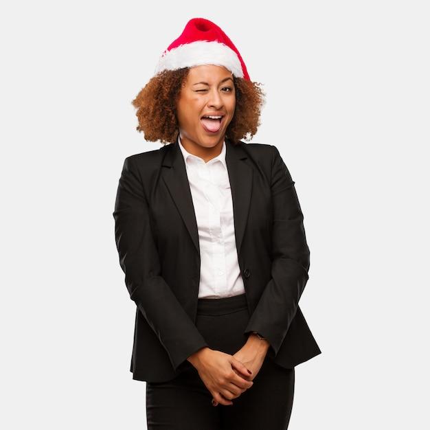 Jovem mulher negra de negócios usando um chirstmas santa chapéu funnny e amigável mostrando a língua Foto Premium