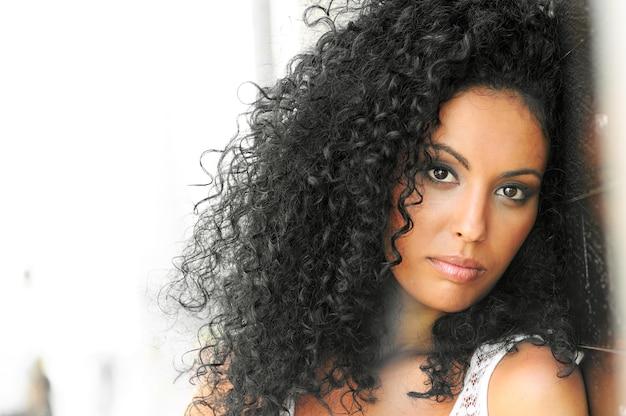 Jovem, mulher negra, penteado afro, em fundo urbano Foto Premium
