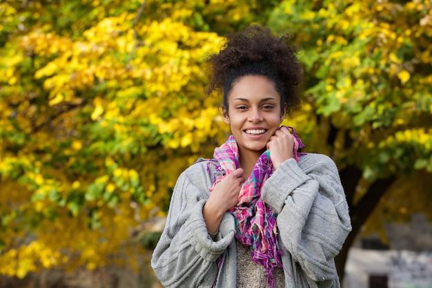 Jovem mulher negra sorrindo ao ar livre no outono | Foto Premium
