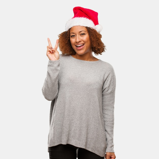 Jovem mulher negra vestindo um chapéu de papai noel divertido e feliz fazendo um gesto de vitória Foto Premium
