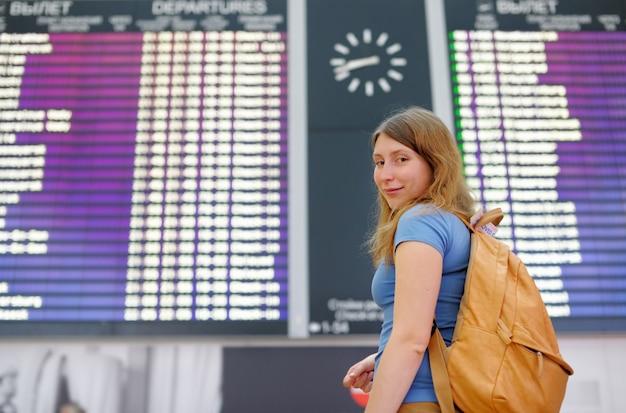 Jovem mulher no aeroporto internacional, com placa de vôo Foto Premium