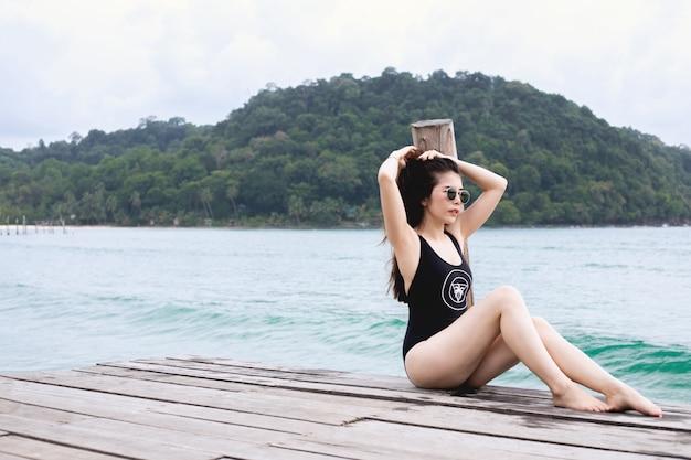 Jovem mulher no banho de sol do roupa de banho na praia do cais no mar, conceito das férias de verão. Foto Premium