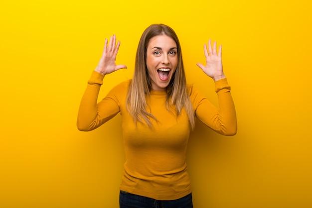 Jovem mulher no fundo amarelo com surpresa e expressão facial chocada Foto Premium