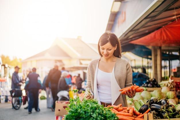 Jovem mulher no mercado comprando legumes. Foto Premium