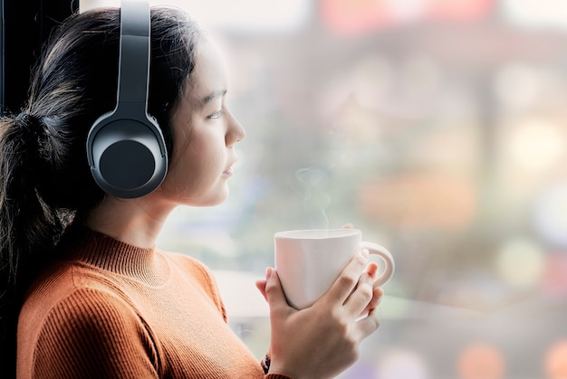 Jovem mulher no musice de escuta da camisola alaranjada e copo da terra arrendada ao estar pela janela. Foto Premium