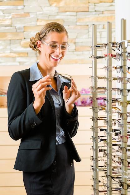 Jovem mulher no oculista com óculos, ela pode ser cliente ou vendedor Foto Premium