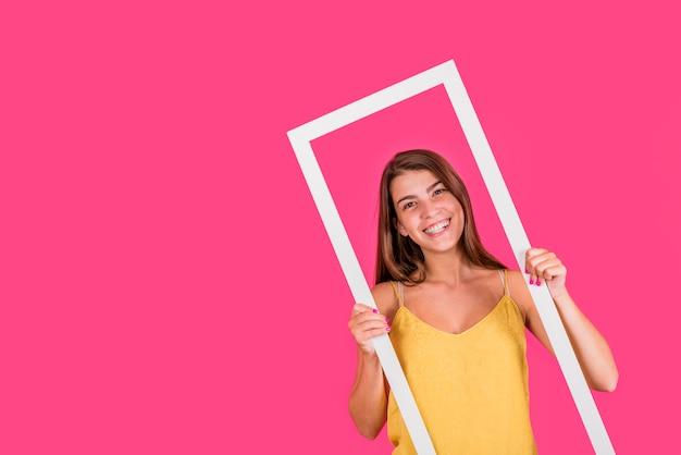 Jovem mulher no quadro branco no fundo rosa Foto gratuita