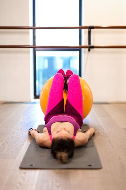 Jovem mulher no sportwear esporte exercício sagacidade fitball amarelo no ginásio. conceito de estilo de vida fitness e bem-estar Foto Premium