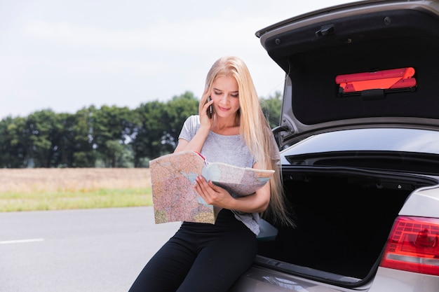 Jovem mulher olhando mapa plano médio Foto gratuita