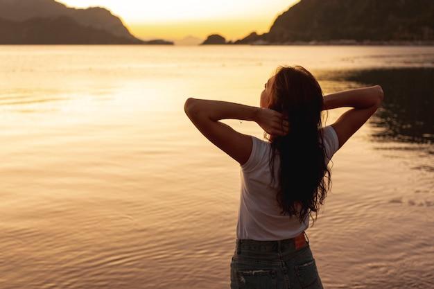 Jovem mulher olhando o pôr do sol na margem de um lago Foto gratuita