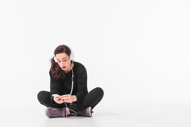 Jovem mulher ouvindo música através de fone de ouvido no mp3 player Foto gratuita