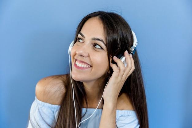 Jovem mulher ouvindo música com fones de ouvido Foto gratuita