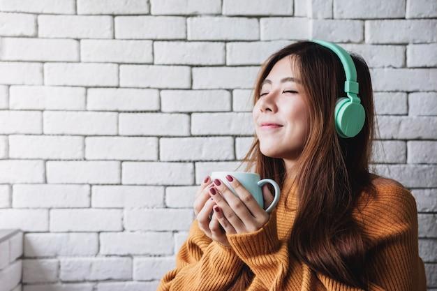 Jovem mulher ouvindo música do fone de ouvido na casa aconchegante Foto Premium