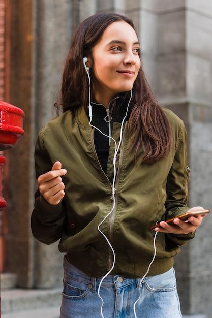 Jovem mulher ouvindo música no fone de ouvido anexar ao telefone móvel Foto gratuita