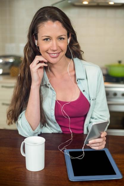 Jovem mulher ouvindo música no smartphone com tablet e caneca de café na bancada da cozinha Foto Premium