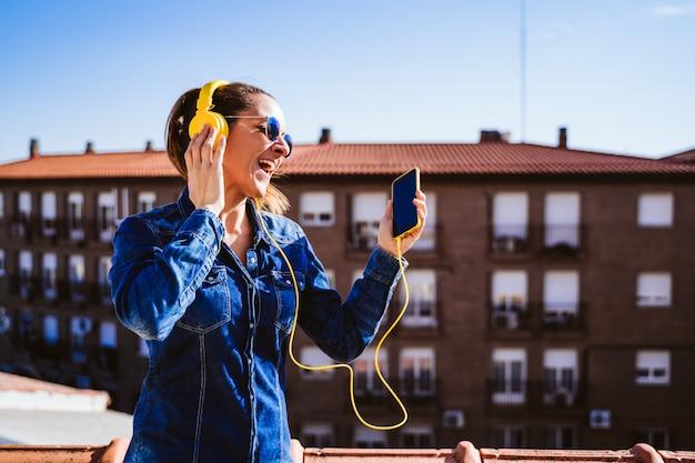 Jovem mulher ouvindo música no telefone celular e fone de ouvido amarelo. diversão e estilo de vida Foto Premium