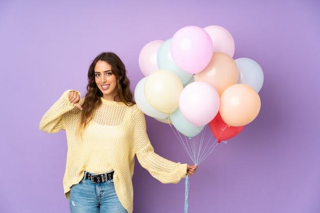 Jovem mulher pegando muitos balões orgulhosos e satisfeitos Foto Premium