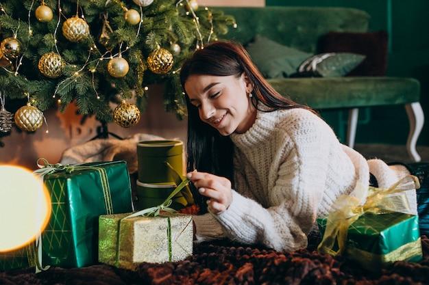 Jovem mulher pela árvore de natal desembalar presentes Foto gratuita