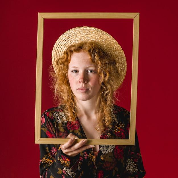 Jovem mulher pensativa do gengibre que guarda o frame de retrato Foto gratuita