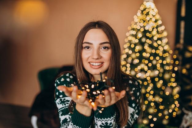 Jovem mulher perto da árvore de natal com luzes brilhantes de natal Foto gratuita