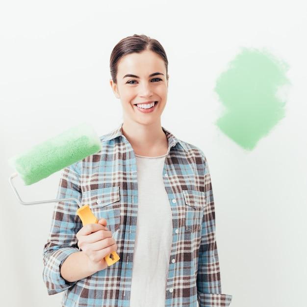 Jovem mulher pintando sua casa Foto Premium