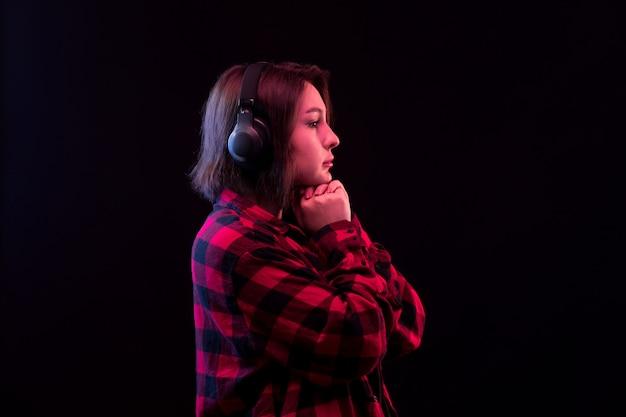 Jovem mulher posando com camisa vermelha e preta quadriculada Foto gratuita