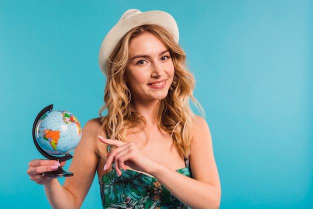 Jovem mulher positiva atrativa no chapéu e no vestido que mostra o globo Foto gratuita