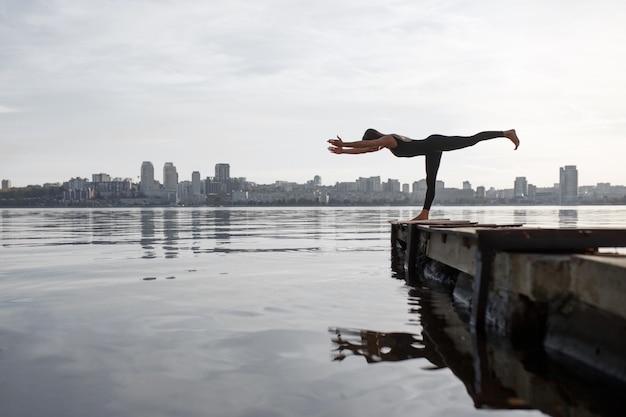 Jovem mulher praticando exercícios de ioga no cais de madeira tranquilo com fundo de cidade. esporte e recreação na cidade Foto Premium