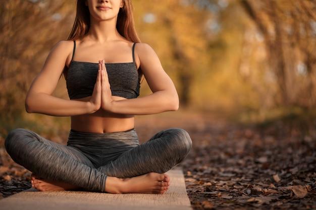 Jovem mulher praticando exercícios de ioga no parque outono com folhas amarelas. estilo de vida esportivo e recreativo Foto Premium