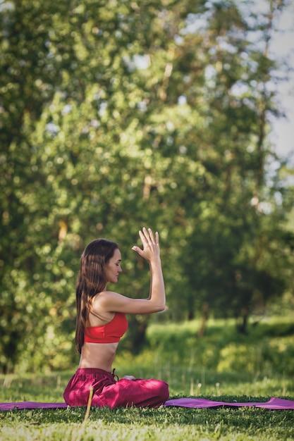 Jovem mulher praticando ioga ao ar livre. feminino meditar ao ar livre no parque da cidade de verão. Foto Premium