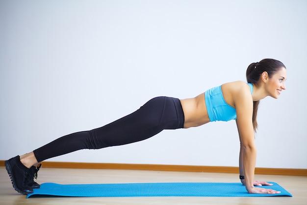 Jovem mulher praticando ioga, fazendo coisa selvagem, exercício flip-the-dog, pose de camatkarasana, malhando, vestindo roupas esportivas, calça preta e blusa, comprimento total interior, parede cinza no estúdio de yoga Foto Premium