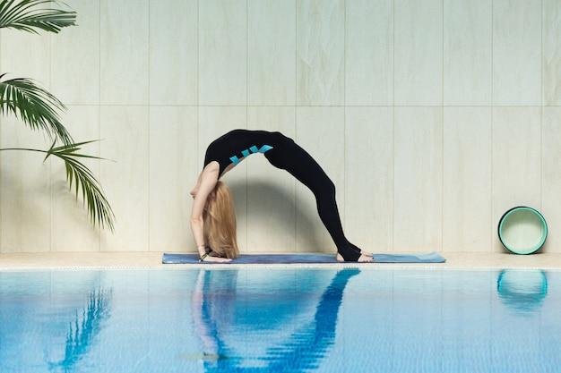 Jovem mulher praticando ioga interior na zona térmica da piscina. Foto Premium
