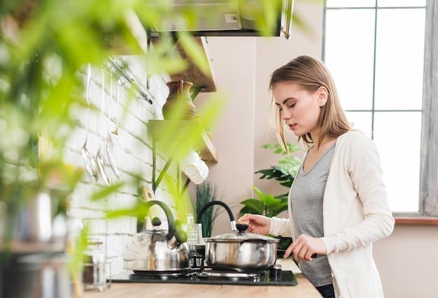 Jovem mulher preparando a comida na cozinha Foto gratuita