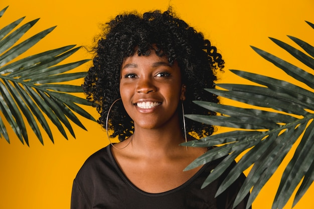 Jovem mulher preta alegre com as folhas tropicais no estúdio Foto gratuita