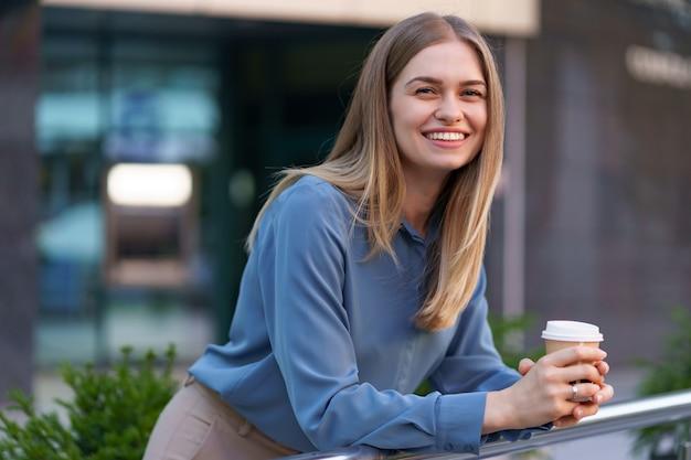 Jovem mulher profissional sorridente, fazendo uma pausa para o café durante seu dia inteiro de trabalho. ela segura um copo de papel ao ar livre perto do prédio comercial, enquanto relaxa e aprecia sua bebida. Foto gratuita