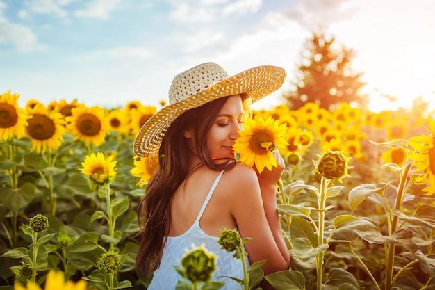 jovem-mulher-que-anda-no-campo-de-florescencia-do-girassol-e-que-cheira-flores_106029-344.jpg