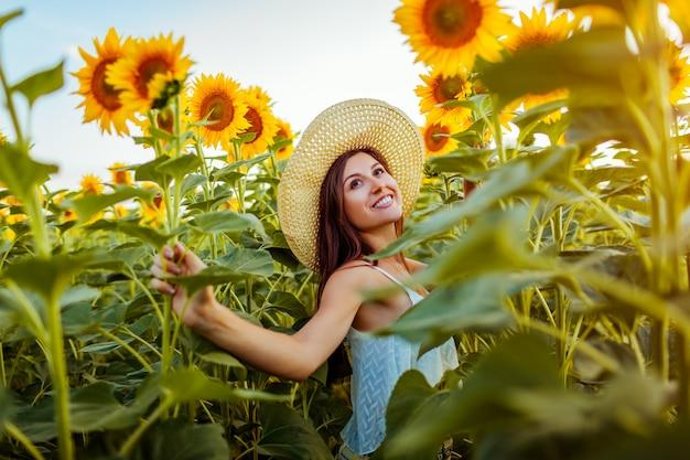 Jovem mulher que anda no campo de florescência do girassol que sente livre e que admira a natureza. Foto Premium