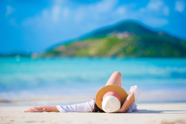 Jovem mulher que aprecia o sol que sunbathing pelo oceano perfeito de turquesa. Foto Premium