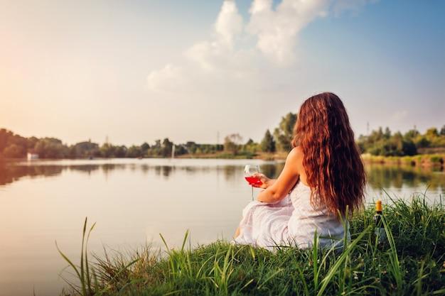 Jovem mulher que aprecia o vidro do vinho no banco de rio no por do sol. mulher, admirar, paisagem, tendo, bebida Foto Premium