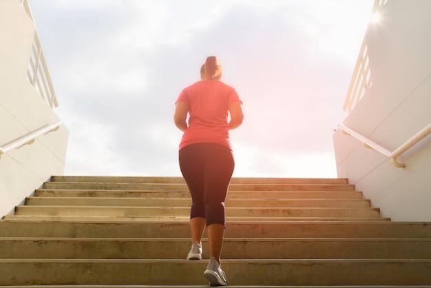 Jovem mulher que corre acima nas escadas de pedra com fundo do ponto do sol. conceito de treino e dieta. Foto Premium